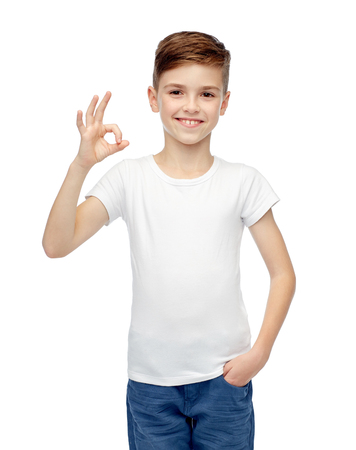 pre adolescent boy: childhood, fashion, advertisement and people concept - happy boy in white t-shirt and jeans showing ok hand sign