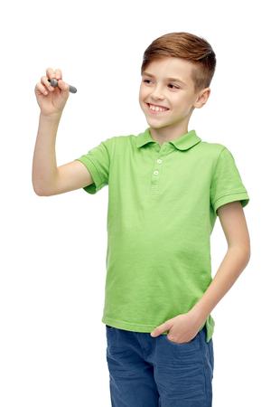 niños escribiendo: la infancia, la educación, la escuela y el concepto de la gente - feliz niño sonriente en verde camiseta del polo con marcador escribiendo algo