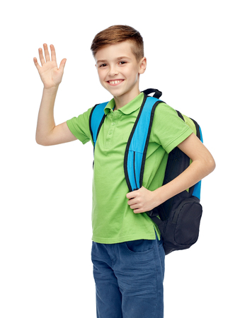 pre adolescent boys: childhood, school, education, greeting gesture and people concept - happy smiling student boy with school bag waving hand