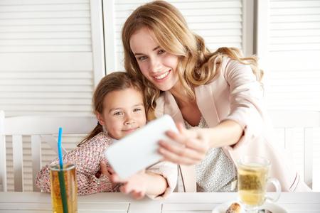 madre soltera: la familia, la paternidad, la tecnología y la gente conceptuales - feliz madre y la niña cenando y tomando selfie por teléfono inteligente en el restaurante