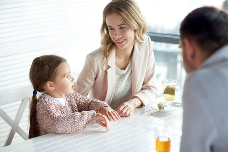 family, parenthood, communication and people concept - happy mother, father and little girl having dinner and talking at restaurant or cafe. Stock Photo