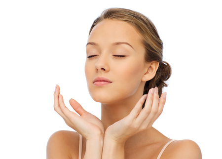 beauty, people, skincare and health concept - young woman face and hands Foto de archivo