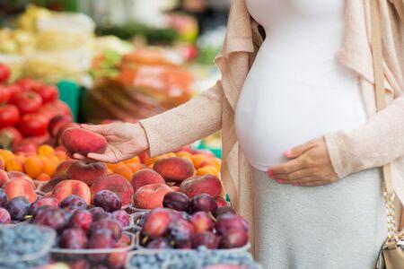Verkauf, Einkaufen, Schwangerschaft und Menschen Konzept - Nahaufnahme der schwangeren Frau, die Wahl saturn Pfirsiche auf Straße Lebensmittel-Markt