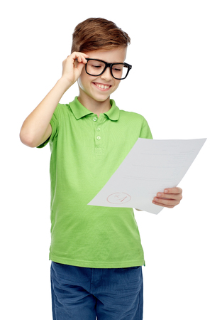 pre teen boys: childhood, school, education and people concept - happy smiling boy in eyeglasses holding paper with test result