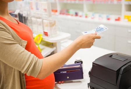 pagando: la medicina, la industria farmacéutica, la salud y las personas concepto - cerca de la mujer embarazada que da el dinero y la compra de medicamentos en la caja registradora de la farmacia Foto de archivo