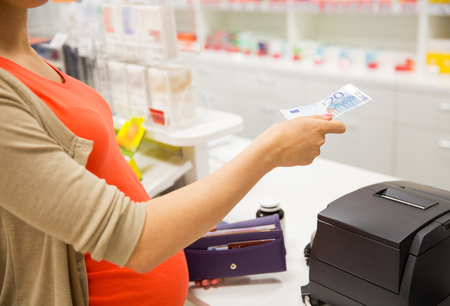 paying: medicine, pharmaceutics, health care and people concept - close up of pregnant woman giving money and buying medication at cash register in drugstore