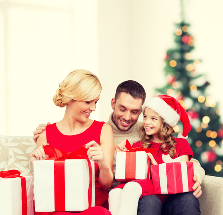 happy christmas: family, christmas, x-mas, winter, happiness and people concept - happy family opening Stock Photo