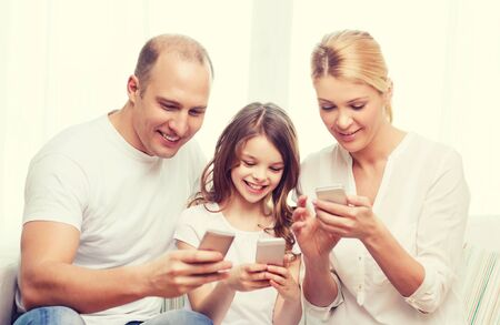 pre adult: family, child, technology and home concept - smiling parents and little girl with smartphones at home