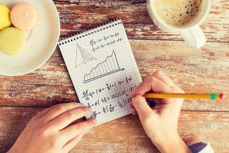 los negocios, la educación y el concepto de la gente - cerca de las manos femeninas con un lápiz, café y galletas para resolver tareas o escribiendo ecuación matemática a cuaderno Foto de archivo