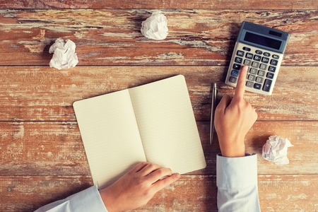 cramped space: business, education, people and technology concept - close up of female hands with calculator, pen and notebook on table