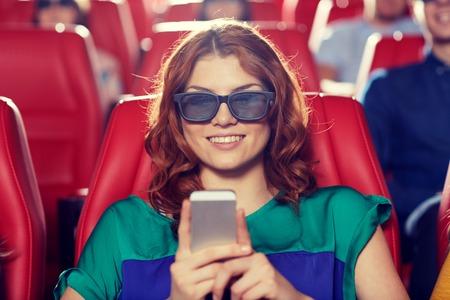 teatro: el cine, la tecnolog�a, el entretenimiento y la gente concepto - mujer feliz con gafas 3d y lectura de mensajes de tel�fonos inteligentes en cine