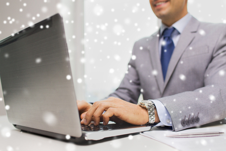 financial audit: business, people, paperwork and technology concept - close up of smiling businessman with laptop computer and papers working in office over snow effect Stock Photo