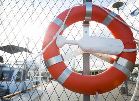 sailing, safety and life rescuing concept - lifebuoy hanging on fence over moored boats on pier Stock Photo