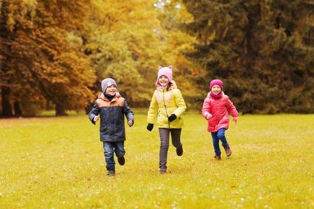 ni�as jugando: oto�o, la infancia, el ocio y el concepto de la gente - grupo de felices los ni�os peque�os que juegan al juego de etiquetas y que se ejecutan en parque al aire libre