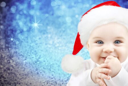 babyhood: christmas, babyhood, childhood and people concept - happy baby in santa hat over blue glitter holidays lights background