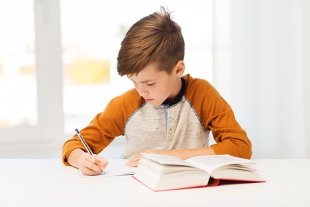 homework: education, childhood, people, homework and school concept - student boy with book writing to notebook at home