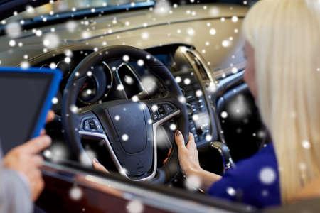alzando la mano: negocio de los automóviles, la venta de coches, la tecnología y el concepto de la gente - cerca de la mujer y del distribuidor de coche manos con ordenador Tablet PC en salón del automóvil o salón de más de efecto de nieve Foto de archivo