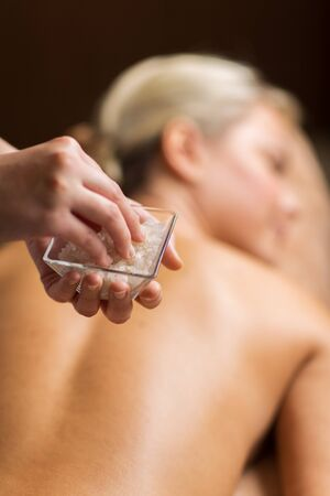 spa therapy: people, beauty, massage and relaxation concept - close up of young woman lying and therapist holding salt bowl in spa Stock Photo