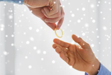 educacion sexual: personas, homosexualidad, sexo seguro, la educación sexual y el concepto de la caridad - Cerca de feliz pareja manos de los homosexuales varones que dan condón sobre el efecto de la nieve