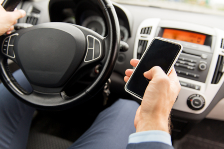 driving: transport, business trip, technology and people concept - close up of young man hand with smartphone driving car Stock Photo