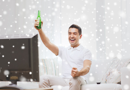 non alcoholic beer: home, people, technology and entertainment concept - smiling man with remote control watching tv and drinking beer at home over snow effect Stock Photo