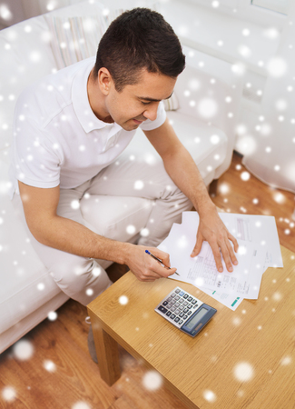 business savings: business, savings, finances and people concept - man with papers and calculator at home counting and filling tax form over snow effect Stock Photo