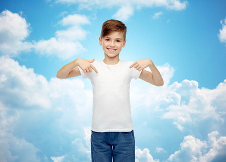 pre teen boy: childhood, fashion, advertisement and people concept - happy boy in white t-shirt and jeans pointing finger to himself over blue sky and clouds background
