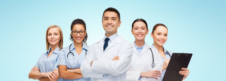 profession: medicine, profession, teamwork and healthcare concept - international group of smiling medics or doctors with clipboard and stethoscopes over blue background