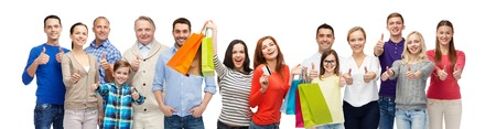 gebaar, verkoop en mensen concept - groep van lachende mannen, vrouwen en kinderen zien thumbs up en het bedrijf boodschappentassen met creditcard
