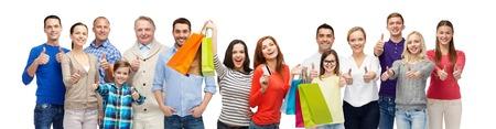 Geste, den Verkauf und die Menschen Konzept - Gruppe lächelnde Männer, Frauen und Kinder, die sich Daumen zeigt und mit Einkaufstaschen mit Kreditkarte Standard-Bild