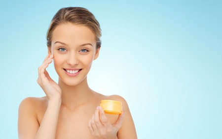 aging face: beauty, people, cosmetics, skincare and cosmetics concept - happy young woman applying cream to her face over blue background