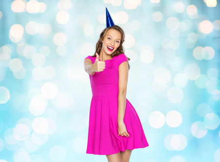posing  agree: people, holidays and celebration concept - happy young woman or teen girl in pink dress and party cap over blue holidays lights background