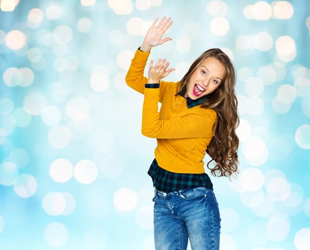 people laughing: people, style and fashion concept - happy young woman or teen girl in casual clothes having fun and applauding over blue holidays lights background