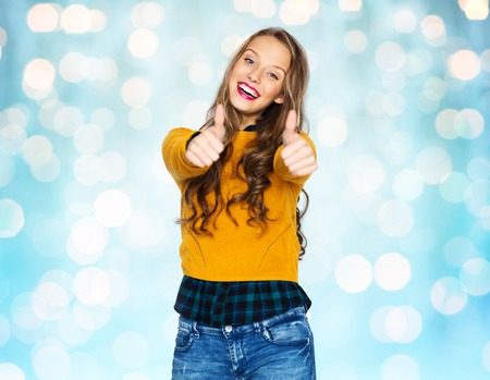 posing  agree: people, gesture, style and fashion concept - happy young woman or teen girl in casual clothes showing thumbs up over blue holidays lights background Stock Photo