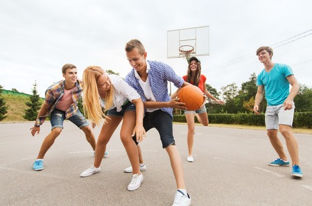 playground basketball: summer vacation, sport, games and friendship concept - group of happy teenagers playing basketball outdoors