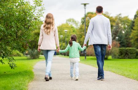 familie, ouderschap, adoptie en de mensen concept - gelukkige moeder, vader en meisje lopen in de zomer park