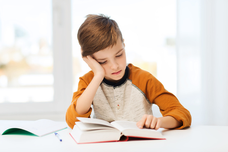 boy room: education, childhood, people, homework and school concept - bored student boy reading book or textbook at home