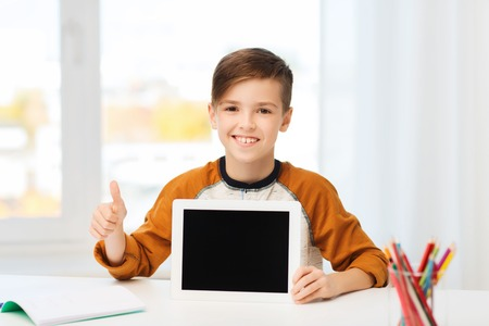 pre approval: leisure, children, technology, education and people concept - smiling boy showing empty tablet pc computer screen and showing thumbs up at home Stock Photo