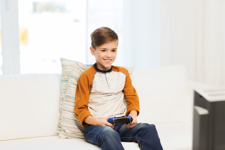 playing video game: leisure, children, technology and people concept - smiling boy with joystick playing video game at home