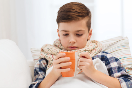 pre teen boy: childhood, healthcare, people and medicine concept - ill boy with flu lying in bed and drinking tea at home