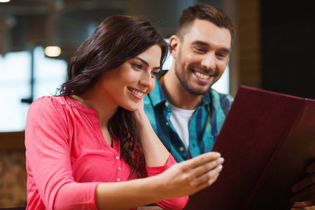 personas leyendo: ocio, personas y concepto de vacaciones - sonriente pareja con menús en el restaurante