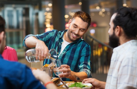 man drinking water: leisure, people and holidays concept - smiling man with friends pouring water from jug at restaurant