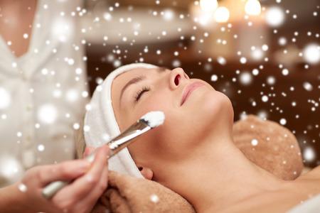 tratamiento facial: personas, belleza, spa, cosmetología y cuidado de la piel concepto - cerca de la hermosa mujer joven tendido con los ojos cerrados y la mano Esteticista aplicar máscara facial con brocha en el salón de spa con efecto de nieve
