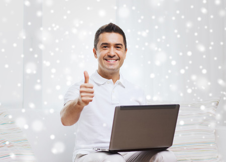 mid distance: technology, people lifestyle and networking concept - happy man with laptop computer showing thumbs up at home over snow effect Stock Photo