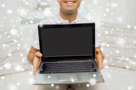 mid distance: technology, people lifestyle and networking concept - close up of happy man showing laptop black blank screen at home over snow effect Stock Photo