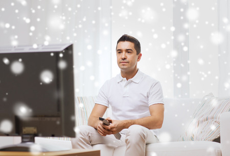 changing channel: home, people, technology and entertainment concept - man with remote control watching tv at home over snow effect