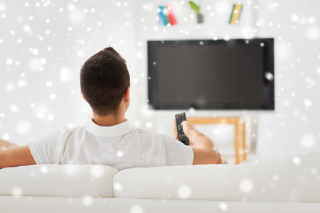 changing channels: leisure, technology, mass media and people concept - man watching tv and changing channels at home from back over snow effect Stock Photo