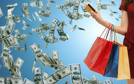 spending: people, sale, finance and consumerism concept - close up of woman with shopping bags and bank or credit card over blue background and money rain