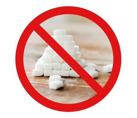 azucar: comida, comida basura, la dieta y la alimentación poco saludable concepto - cerca de la pirámide de azúcar blanco en la mesa de madera sobre el círculo rojo-barra invertida ningún signo