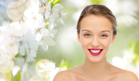 bright colors: beauty, people and health concept - smiling young woman face with pink lipstick on lips and shoulders over summer green natural background with cherry blossom